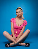 Le jeune femme dans la robe de rose s'asseyent sur le bleu Photo stock