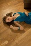 Le jeune femme dans une robe bleue s'étend sur un parquet Images stock