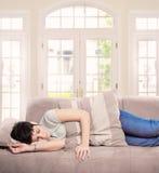 Le jeune femme dort sur le sofa Photographie stock
