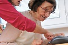 Le jeune femme enseigne son grand-mère Photos libres de droits