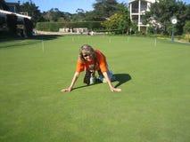 Le jeune femme essaye à l'herbe dense de pelouse sur le golf Image stock
