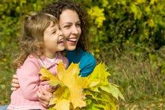 Le jeune femme et la fille rient avec des lames dans le jardin Images stock
