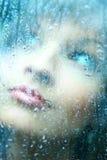 Le jeune femme et une pluie relâche Photographie stock