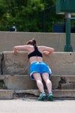 Le jeune femme fait des pousées contre des pas concrets Photos stock