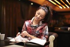 le jeune femme s'asseyant dans le café a affiché le magazine Photographie stock