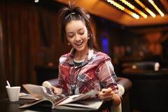 Le jeune femme s'asseyant dans le café a affiché le magazine Photos stock