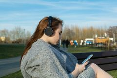 Le jeune, fille rousse heureuse au printemps en parc près de la rivière écoute la musique par les écouteurs sans fil de bluetooth photos libres de droits