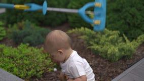 Le jeune fils de bébé garçon a obtenu réduit dans un jardin avec des jouets - scène chaude d'été de couleur de valeurs familiales banque de vidéos