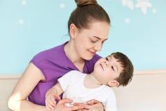 Le jeune fils européen adorable d'étreintes de mère ont la joie ensemble, dépensent le weeknd à la maison contre l'intérieur conf images stock