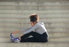 Le jeune folâtre la femme s'asseyant sur des escaliers étirant des muscles de jambe Photographie stock libre de droits