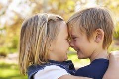 Le jeune frère et la soeur flairent pour flairer en parc, vue de côté Photo libre de droits