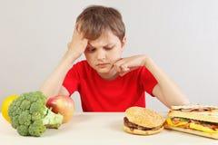 Le jeune garçon à la table choisit entre le prêt-à-manger et le légume et les fruits photos stock