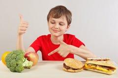 Le jeune garçon à la table choisit entre le prêt-à-manger et l'alimentation saine sur le fond blanc images stock