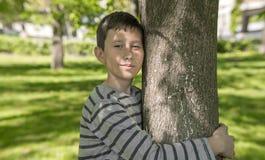 Le jeune garçon étreint un arbre Photos libres de droits