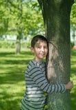 Le jeune garçon étreint un arbre Image stock