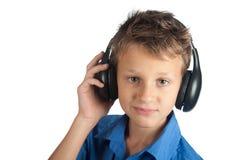Le jeune garçon avec des écouteurs d'isolement sur le fond blanc Image stock