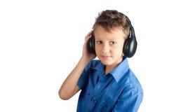 Le jeune garçon avec des écouteurs d'isolement sur le fond blanc Images libres de droits