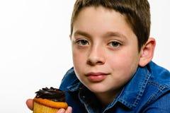 Le jeune garçon avec la chemise de denim mangeant le petit gâteau de chocolat, sur le blanc a isolé le fond Fin vers le haut Image libre de droits