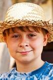 Le jeune garçon avec le chapeau de paille est heureux Image stock