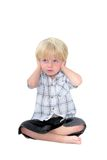Le jeune garçon avec le sien remet ses oreilles et fond blanc Images stock