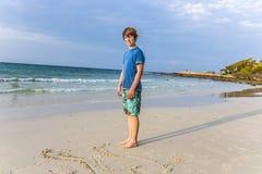Le jeune garçon avec les cheveux rouges apprécie la belle plage Photos libres de droits
