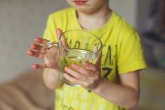 Le jeune garçon, garçon commence son matin avec un verre d'eau douce Le petit garçon bouclé boit l'eau Concept de l'eau Image libre de droits