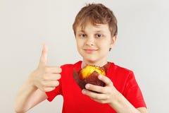 Le jeune garçon coupé dans une chemise rouge recommande le petit pain photographie stock