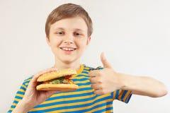 Le jeune garçon coupé recommande et aime le grand hamburger sur le fond blanc photo libre de droits