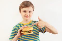 Le jeune garçon coupé recommande l'hamburger sur le fond blanc photos stock