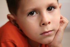 Le jeune garçon a détendu le sourire avec des mains sur le menton Photo libre de droits
