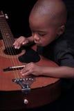 Le jeune garçon d'Afro-américain joue la guitare Image libre de droits