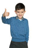 Le jeune garçon dans le pull bleu tient son pouce  Images stock