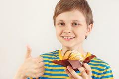 Le jeune garçon dans une chemise rayée recommande le gâteau aux pommes doux sur le fond blanc image stock