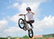Le jeune garçon de cycliste fait des tours dans le ciel Image stock