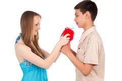 Le jeune garçon donne à une fille un jouet Photographie stock libre de droits