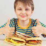 Le jeune gar?on dr?le dans une chemise ray?e ? la table recommande les hamburgers et le sandwich sur le fond blanc image libre de droits