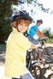Le jeune garçon et son équitation de papa fait du vélo ensemble image libre de droits