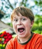 Le jeune garçon fait les visages drôles Photo stock