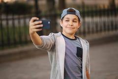 Le jeune garçon font un selfie sur le smartphone au centre de la ville Garçon mignon dans le chapeau bleu Écolier élégant photographie stock