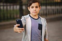 Le jeune garçon font un selfie sur le smartphone au centre de la ville Garçon mignon dans le chapeau bleu Écolier élégant image libre de droits