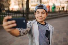 Le jeune garçon font un selfie sur le smartphone au centre de la ville Garçon mignon dans le chapeau bleu Écolier élégant images libres de droits