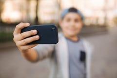 Le jeune garçon font un selfie sur le smartphone au centre de la ville Garçon mignon dans le chapeau bleu Écolier élégant image stock