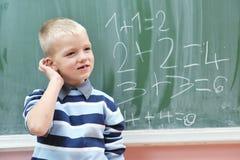 Le jeune garçon heureux aux maths de la première pente classe image stock