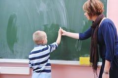 Le jeune garçon heureux aux maths de la première pente classe photos stock