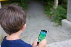 Le jeune garçon jouant Pokemon vont Image stock
