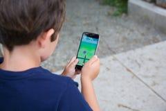 Le jeune garçon jouant Pokemon vont Photographie stock