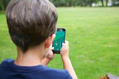 Le jeune garçon jouant Pokemon vont Photographie stock libre de droits