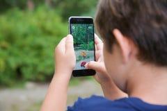 Le jeune garçon jouant Pokemon vont Images libres de droits