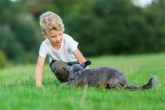 Le jeune garçon joue avec un chien d'hybride de terrier Photographie stock libre de droits