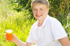 Le jeune garçon juge de verre avec du jus de carotte Photographie stock libre de droits